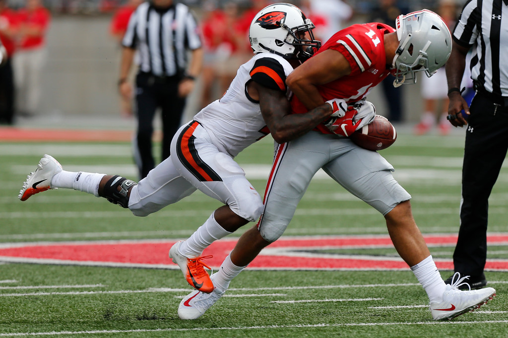 . Oregon State defensive back Dwayne Williams, left, tackles Ohio State receiver Austin Mack during the second half of an NCAA college football game Saturday, Sept. 1, 2018, in Columbus, Ohio. Ohio State beat Oregon State 77-31. (AP Photo/Jay LaPrete)