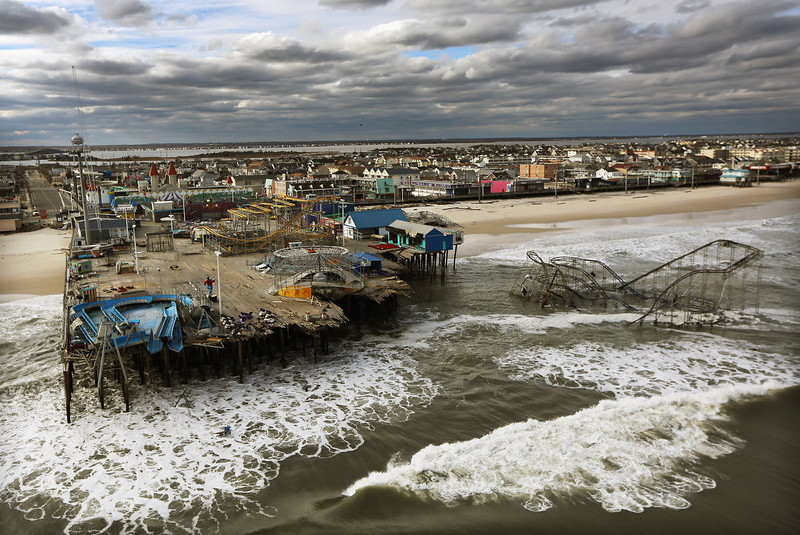 ". Waves break in front of a destroyed amusement park wrecked by Hurricane Sandy on October 31, 2012 in Seaside Heights, New Jersey.  At least 50 people were reportedly killed in the U.S. by Sandy with New Jersey suffering massive damage and power outages. ""Hurricane Sandy\"" was Google\'s number one most searched trending event of 2012. (Photo by Mario Tama/Getty Images)"