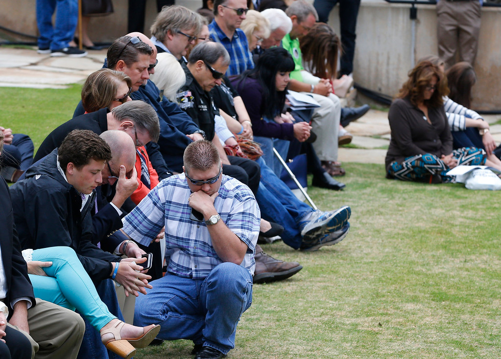 . Spectators bow their heads during a moment of prayer during a ceremony to commemorate the 20th anniversary of the Oklahoma City bombing at the Oklahoma City National Memorial in Oklahoma City, Sunday, April 19, 2015. (AP Photo/Sue Ogrocki)