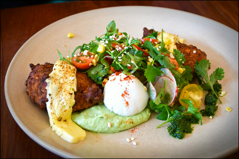 Corn fritters with poached eggs, haloumi and guacamole