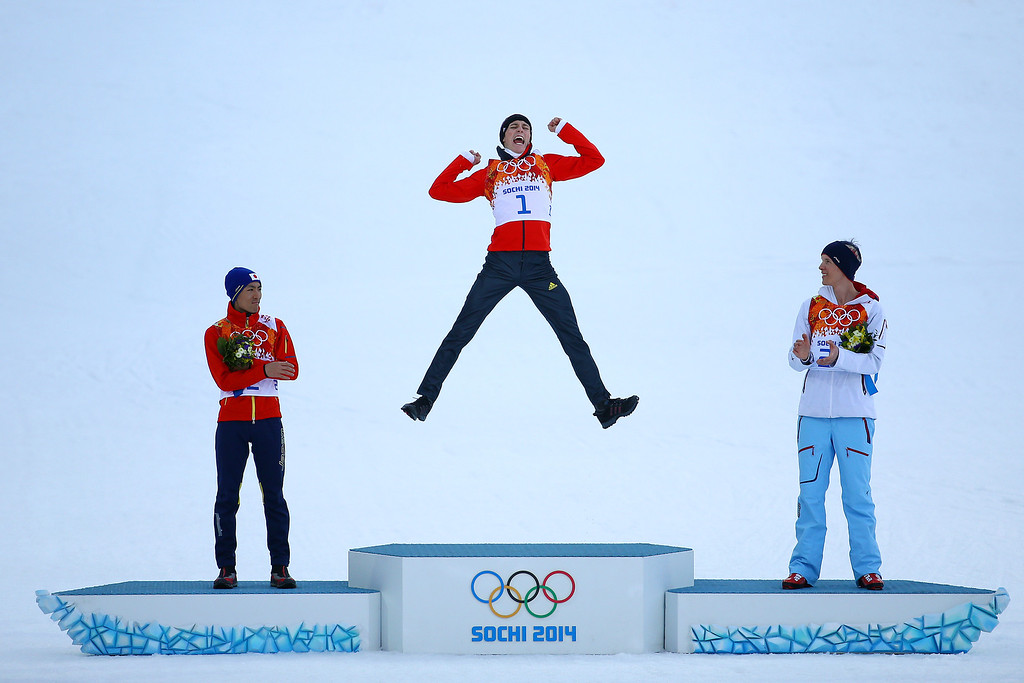 . Gold medalist Eric Frenzel of Germany jumps in celebration alongside silver medalist Akito Watabe of Japan (L) and bronze medalist Magnus Krog of Norway (R) during the flower ceremony for the Men�s Nordic Combined Individual Gundersen Normal Hill and 10km Cross Country on day 5 of the Sochi 2014 Winter Olympics at the RusSki Gorki Nordic Combined Skiing Stadium on February 12, 2014 in Sochi, Russia.  (Photo by Al Bello/Getty Images)