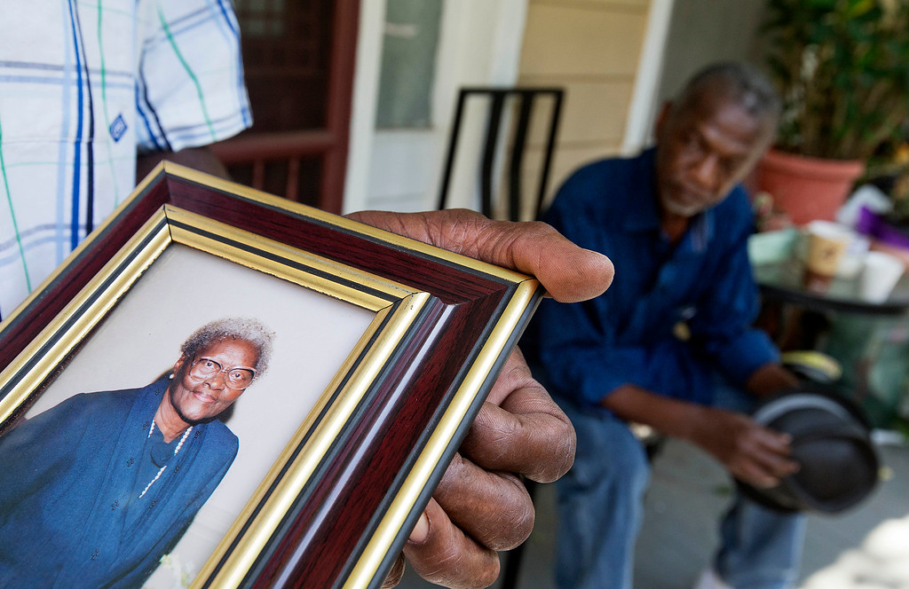 . Walter Jackson holds a photo of his mother Susie Jackson, one of the nine people killed in Wednesday\'s shooting at Emanuel AME Church, as he stands on his front porch with his cousin Kenneth Washington Friday, June 19, 2015, in Charleston, S.C. (AP Photo/David Goldman)