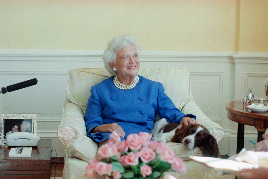 """. First lady Barbara Bush, with her pet dog Millie, talks to reporters in Washington, Sept. 11, 1990. Mrs. Bush said Iraq cannot be allowed to get away with its occupation of Kuwait. She also revealed that Millie has a case of lupus but """"she\'s in complete remission."""" (AP Photo/Charles Tasnadi)"""