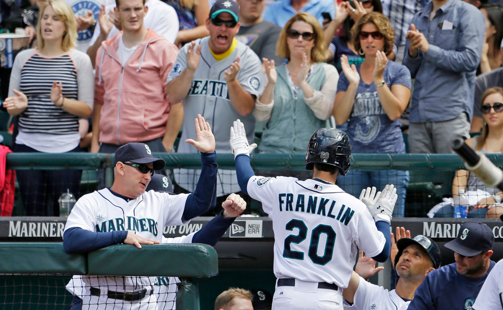 . Seattle\'s Nick Franklin is congratulated as he enters the dugout following his solo home run against the Twins in the seventh inning. (AP Photo/Elaine Thompson)