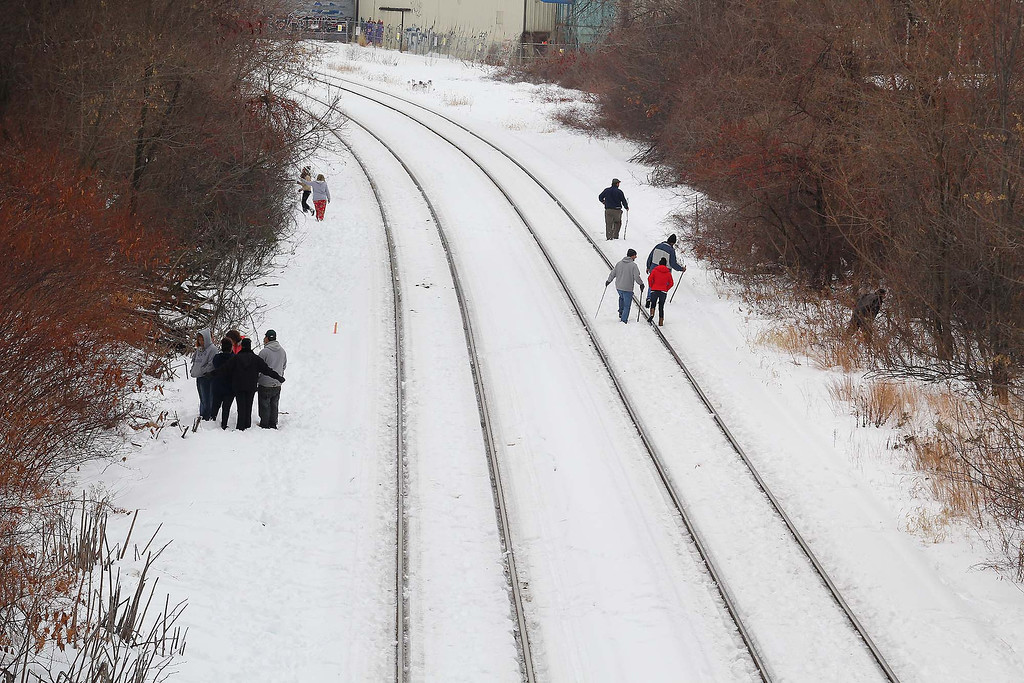 . Volunteers help search the tracks near Rollstone Street for Jeremiah Oliver, 5, on Saturday in Fitchburg. SENTINEL & ENTERPRISE/JOHN LOVE