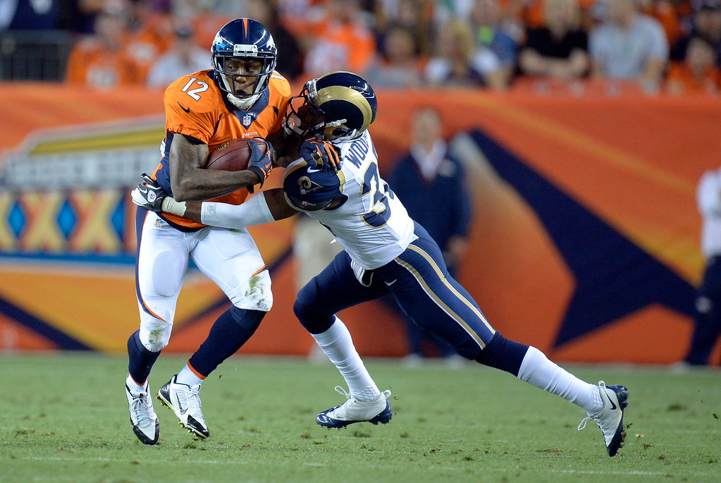 . DENVER, CO. - AUGUST 17: Denver Broncos wide receiver Andre Caldwell (12) picks up some yards as St. Louis Rams defensive back Darren Woodard (35) comes in for the tackle during the third quarter August 24, 2013 at Sports Authority Field at Mile High. (Photo By John Leyba/The Denver Post)