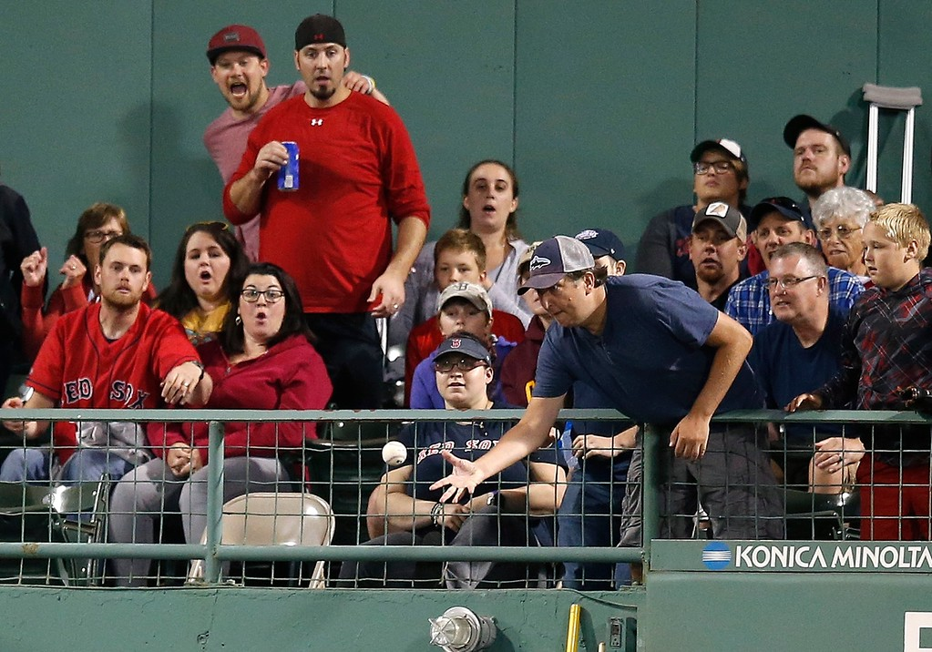 . A fan reaches for the home run ball from Cleveland Indians\' Melky Cabrera during the sixth inning of a baseball game against the Boston Red Sox in Boston, Tuesday, Aug. 21, 2018. (AP Photo/Michael Dwyer)