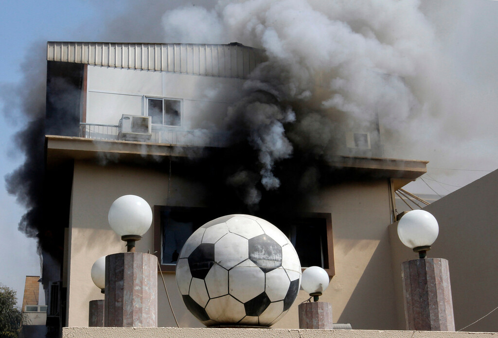 . Smoke rises from the Egyptian Soccer Federation after protesters set fire following a court verdict, in Cairo, Egypt, Saturday, March 9, 2013..(AP Photo/Amr Nabil)