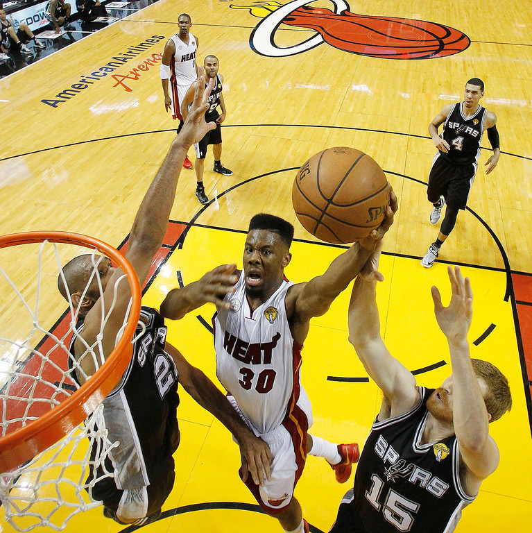 . Miami Heat point guard Norris Cole (30) shoots against San Antonio Spurs power forward Tim Duncan, left, and San Antonio Spurs power forward Matt Bonner (15) during the first half of Game 1 of basketball\'s NBA Finals, Thursday, June 6, 2013 in Miami. (AP Photo/Mike Segar, Pool)
