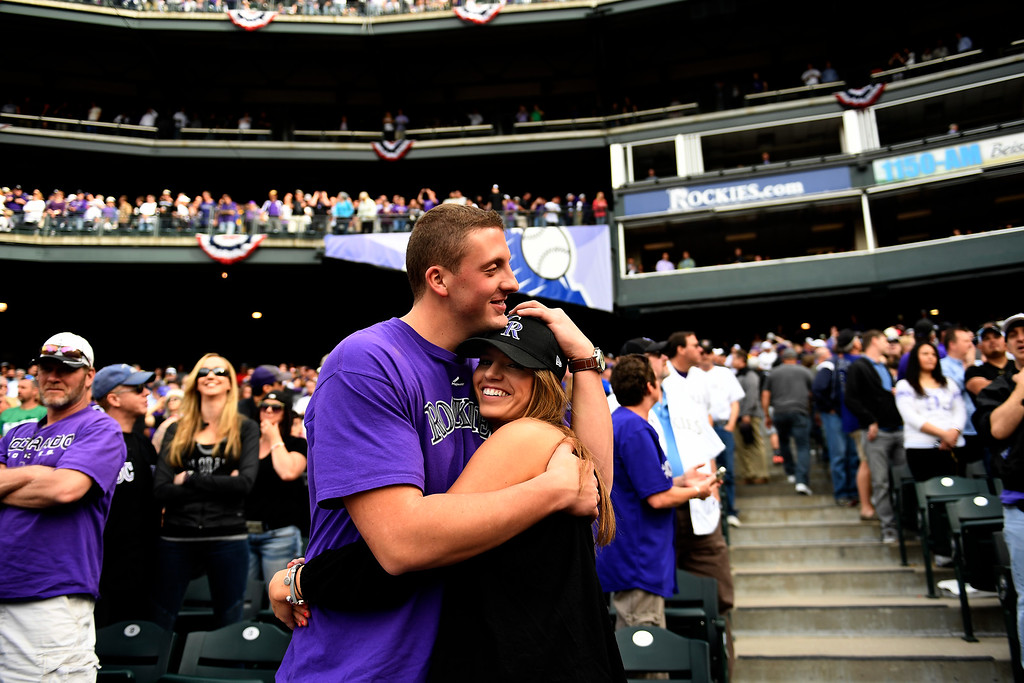 . Denver, CO - ARRIL 08: Connor Center of New York hugs Alex Evans of Denver during the 7th inning stretch at the Colorado Rockies home opener against the San Diego Padres at Coors Field. April 08, 2016 in Denver, CO. (Photo By Joe Amon/The Denver Post)