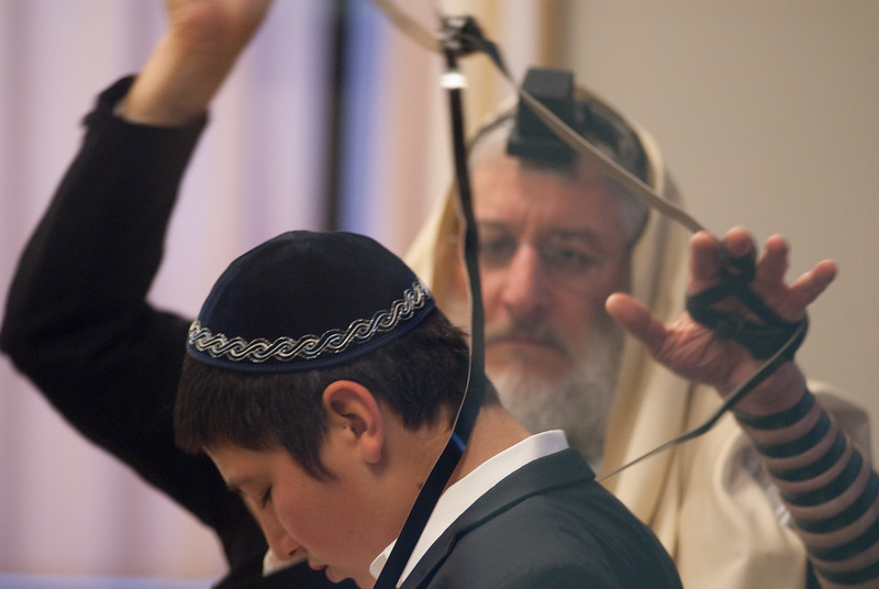 A father is helping his son pray with his tifillian for the first time in preparation for his upcoming Bar mitzvah. The father, Elozor Plotke is a brilliant mechanical engineer who holds many patents used in satillite technology for the US Government. His endeavors are mostly classified.