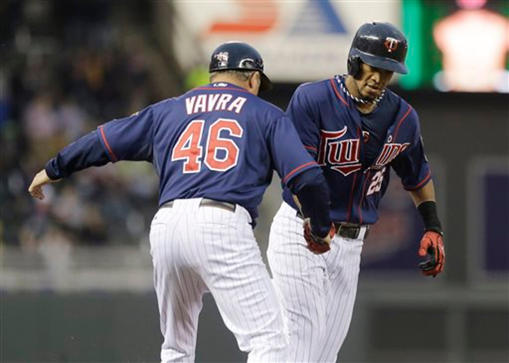 . Minnesota Twins\' Pedro Florimon, right, is congratulated by third-base coach Joe Vavra after his two-run home run off Boston Red Sox pitcher Clay Buchholz in the third  inning.  (AP Photo/Jim Mone)