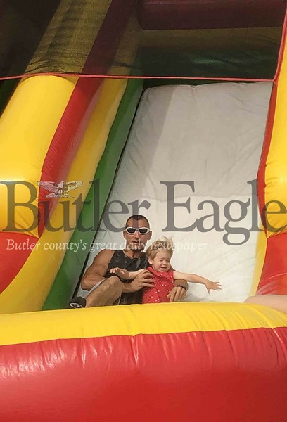 Photo by Michele JurystaMark and son Maverick, 2, of Valencia, ride a slide Saturday during Adams Township Community Day.