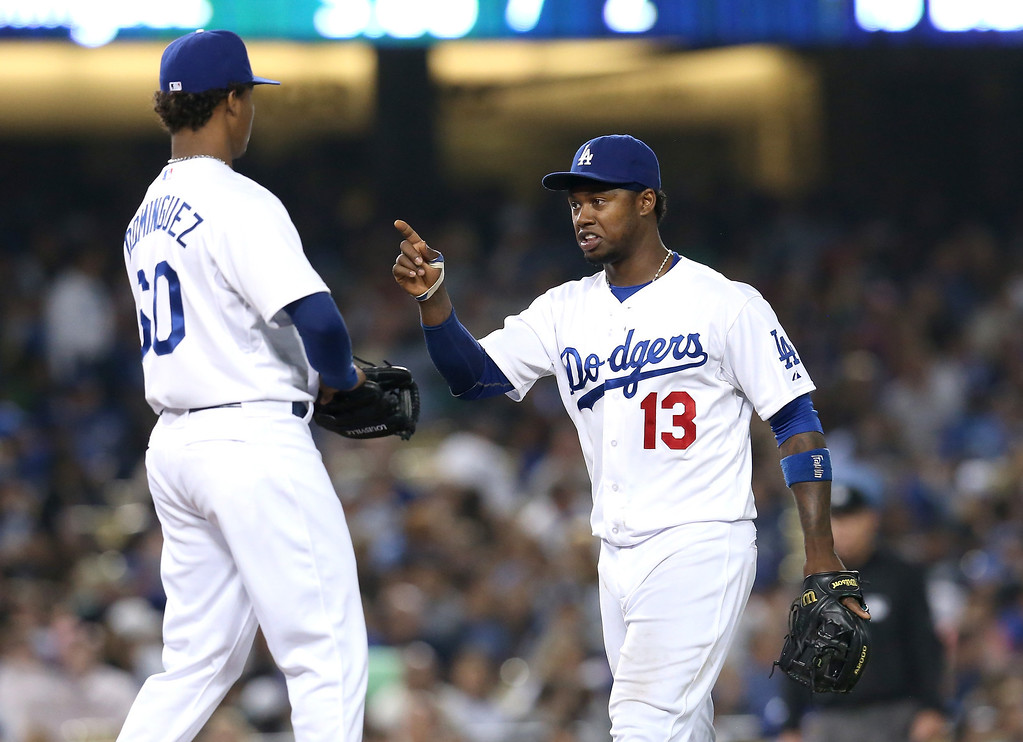 . LOS ANGELES, CA - JULY 12:  Shortstop Hanley Ramirez #13 of the Los Angeles Dodgers confers with relief pitcher Jose Dominguez #60 in the eighth inning against the Colorado Rockies at Dodger Stadium on July 12, 2013 in Los Angeles, California.  (Photo by Stephen Dunn/Getty Images)