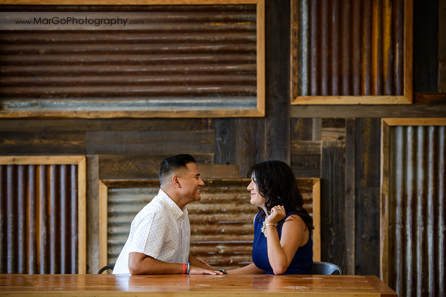 woman in blue dress and man in white shirt sitting at the table and looking at each other during engagement session at San Pedro Square Market in San Jose