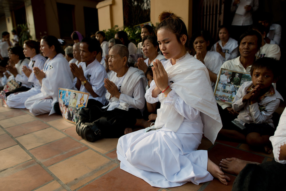 . Cambodian mourners sit and pray in a street at the crematorium where a coffin bearing the remains of Cambodia\'s late King Norodom Sihanouk is placed before his cremation near the Royal Palace in Phnom Penh on February 4, 2013. Thousands of mourners massed in the Cambodian capital as the kingdom cremated its revered former King Norodom Sihanouk, who steered his country through six turbulent decades. AFP PHOTO/ Nicolas  ASFOURI/AFP/Getty Images