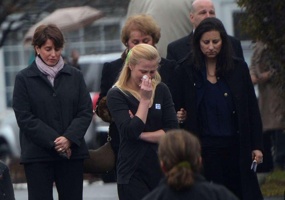 Description of . Mourners leave from Honan funeral home after attending the funeral for Jack Pinto, 6, one of the victims of the Sandy Hook elementary school shooting, on December 17, 2012, in Newtown, Connecticut. Funerals began in the little Connecticut town of Newtown after the school massacre that took the lives of 20 small children and six staff, triggering new momentum for a change to America's gun culture. AFP PHOTO/Emmanuel  DUNAND/AFP/Getty Images