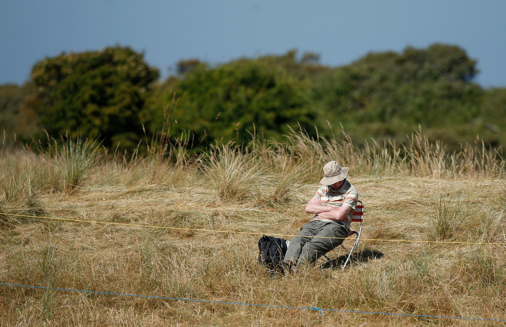 . A spectator sits in the sun during the second round of the British Open Golf Championship at Muirfield, Scotland, Friday July 19, 2013. (AP Photo/Matt Dunham)