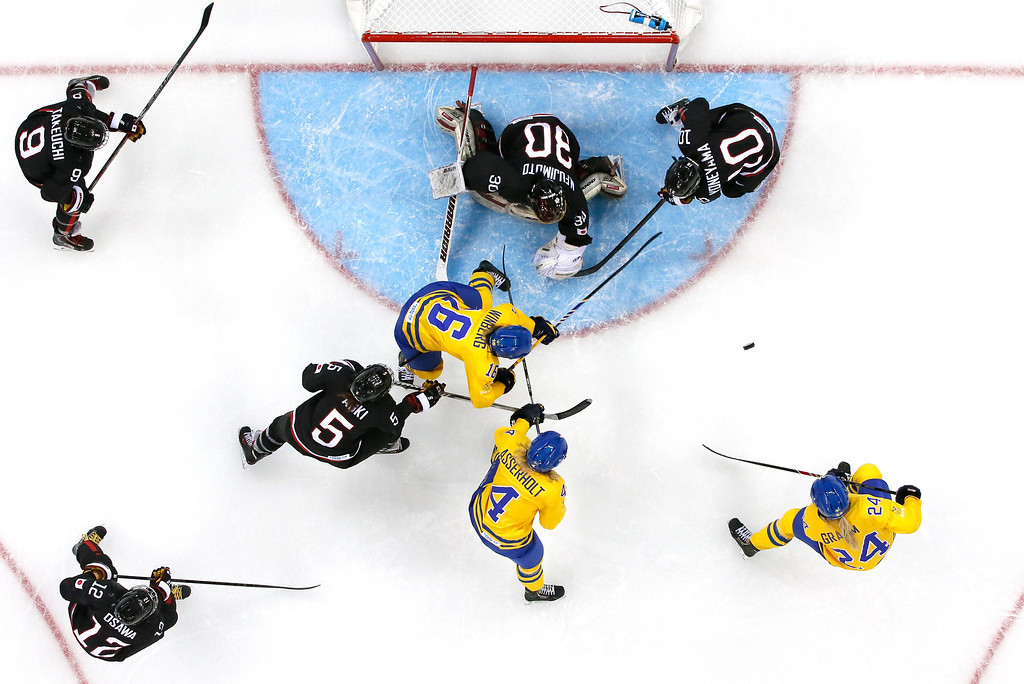 . Players of Japan (black) and Sweden chase the puck in front of the Japanese goal during the women\'s match between Sweden and Japan at the Shayba Arena in the Ice Hockey tournament at the Sochi 2014 Olympic Games, Sochi, Russia, 09 February 2014.  EPA/LARRY SMITH
