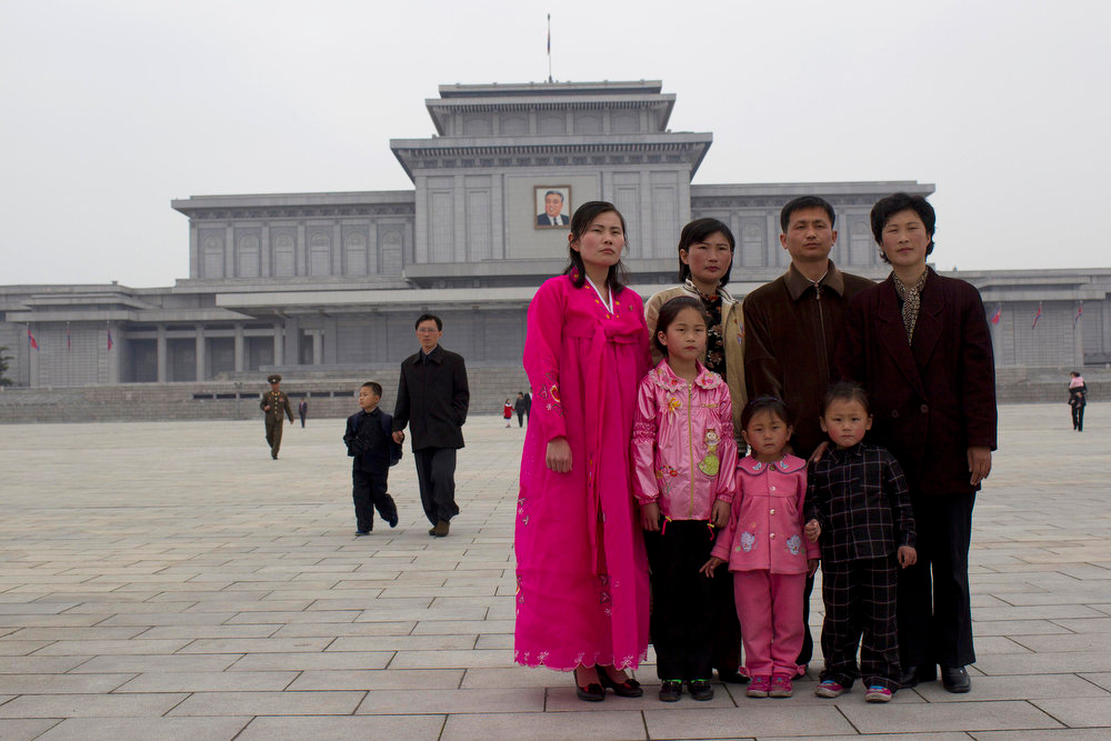 Description of . A North Korean family prepares to have their photo taken during a holiday to mark the 99th anniversary of Kim Il Sung's birthday at the Kumsusan Memorial Palace, where the body of late Kim Il Sung lay in state, in Pyongyang, North Korea on Friday April 15, 2011. April 15 is called 'The Day of the Sun' in honor of the former guerrilla fighter who founded North Korea in 1948.  (AP Photo/David Guttenfelder)