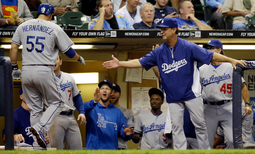 . Los Angeles Dodgers manager Don Mattingly, right, congratulates Ramon Hernandez (55) after his home run during the third inning of a baseball game against the Milwaukee Brewers Wednesday, May 22, 2013, in Milwaukee. (AP Photo/Morry Gash)