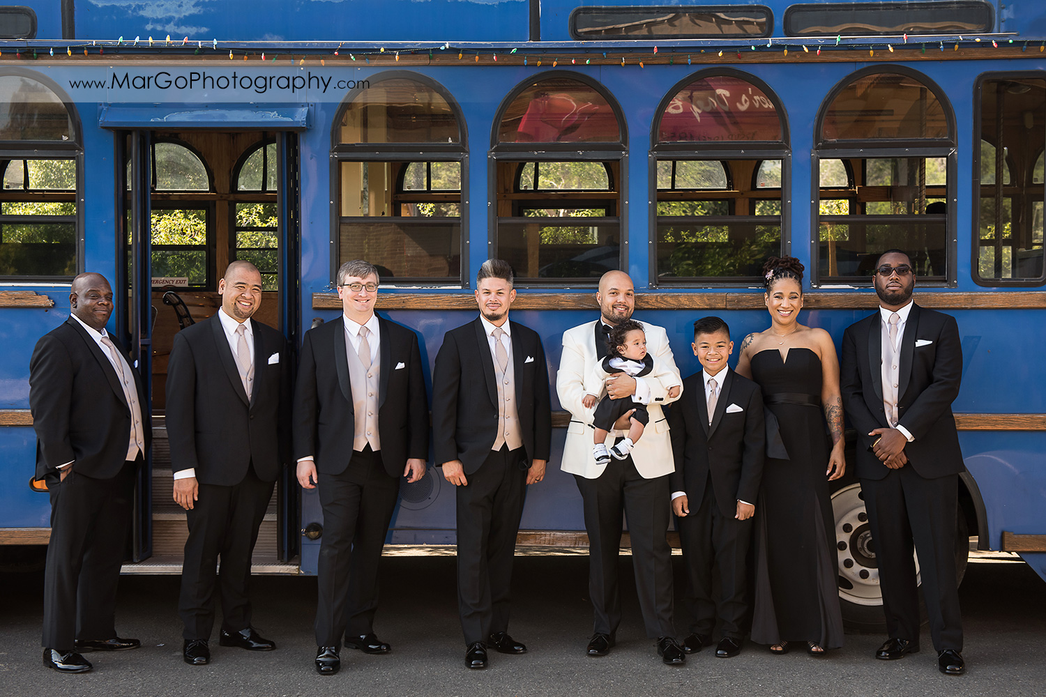 groom and groomsmen in front of blue tram at Sunol's Casa Bella