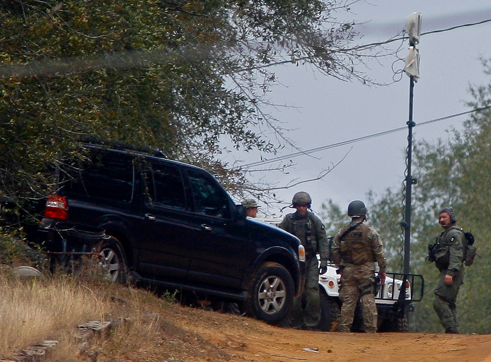 Description of . Law enforcement personnel stand at the perimeter of the scene of a shooting and hostage taking in Midland City, Alabama, January 30, 2013. A gunman boarded an Alabama school bus ferrying children home from school on Tuesday and fatally shot the driver before fleeing with a young child and holing up in an underground bunker, Alabama media reported. Sheriff's officials confirmed that one person had been killed in a shooting involving a school bus in Alabama's Dale County but gave scant details other than to say that a child was present at the scene in Midland City. REUTERS/Phil Sears