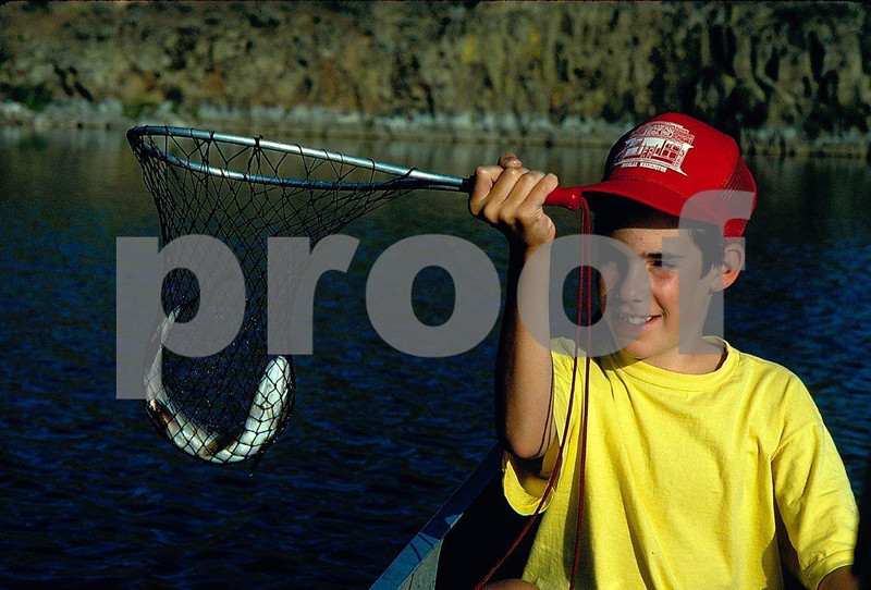 Young boy proudly displays a trout he caught.