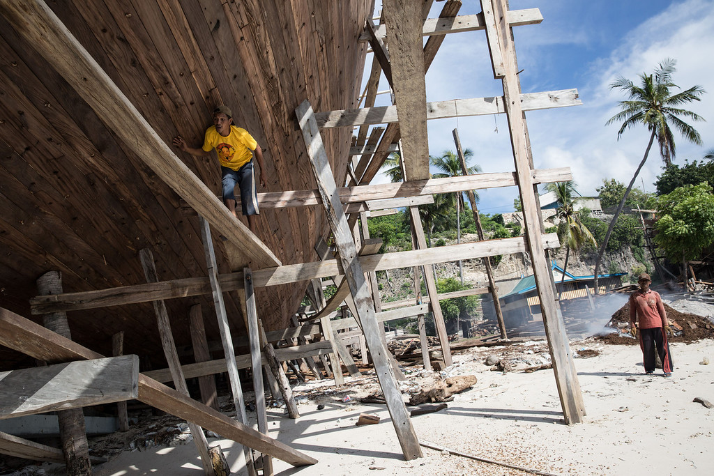 . A Buginese man works as he make sure the hull of phinisi is finished at Tanjung Bira Beach on May 2, 2014 in Bulukumba, South Sulawesi, Indonesia. (Photo by Agung Parameswara/Getty Images)
