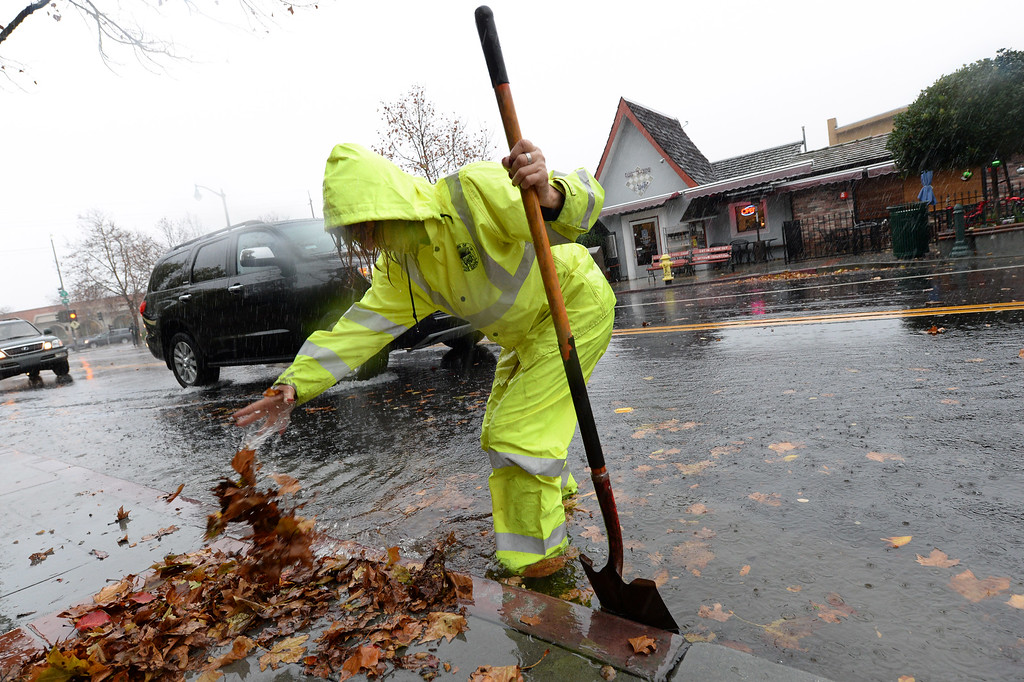 . City worker Sherrie Olsen clears a storm drain along N. Santa Cruz Avenue in Los Gatos, Calif., on Thursday, Dec. 11, 2014. The big storm made its way south, after pounding the North Bay in the early morning hours. (Dan Honda/Bay Area News Group)