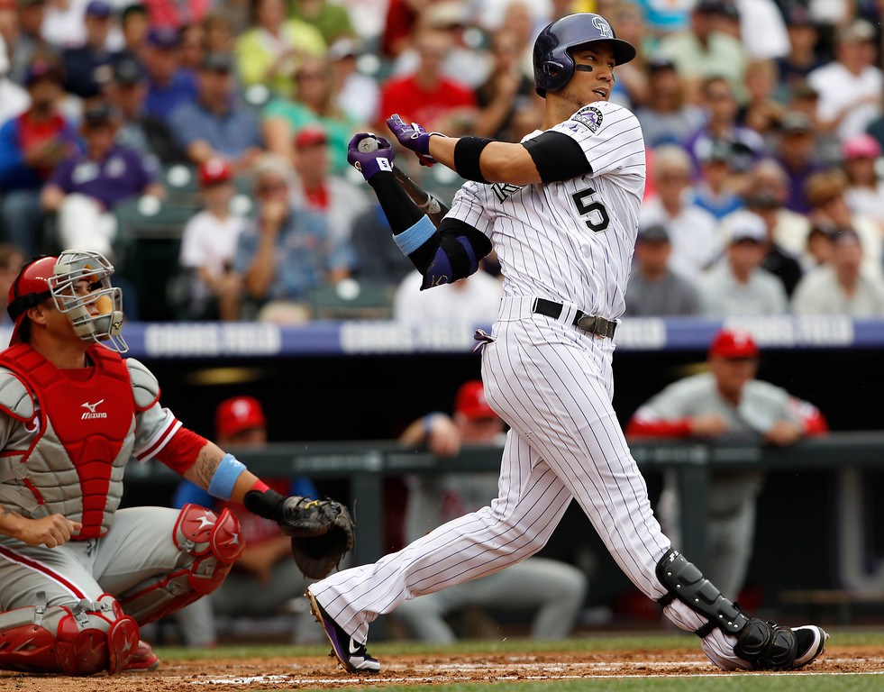 . Colorado Rockies\' Carlos Gonzalez, right, pops out as Philadelphia Phillies catcher Humberto Quintero looks on in the first inning of a baseball game in Denver, Sunday, June 16, 2013. (AP Photo/David Zalubowski)