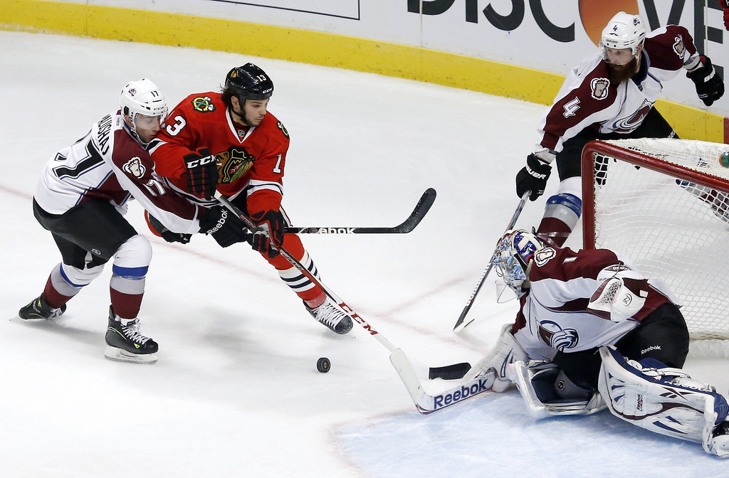 . Chicago Blackhawks left wing Daniel Carcillo (13) is unable to get a rebound off his shot on Colorado Avalanche goalie Semyon Varlamov (1), of Russia, as Aaron Palushaj (17) and Greg Zanon defend during the second period of an NHL hockey game, Wednesday, March 6, 2013, in Chicago. (AP Photo/Charles Rex Arbogast)