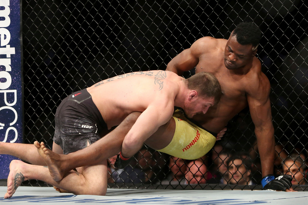 . Stipe Miocic, left, takes down Francis Ngannou during a heavyweight championship mixed martial arts bout at UFC 220, early Sunday, Jan. 21, 2018, in Boston. Miocic retained his title via unanimous decision. (AP Photo/Gregory Payan)