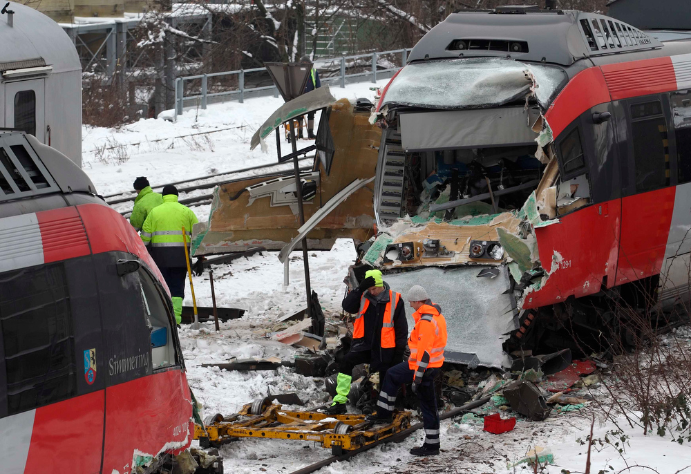 . Workers stand next to two demolished S45 trains after a train crash in Vienna January 21, 2013. Two trains collided Monday morning, injuring 25 people, police said. REUTERS/Heinz-Peter Bader (AUSTRIA - Tags: DISASTER TRANSPORT)
