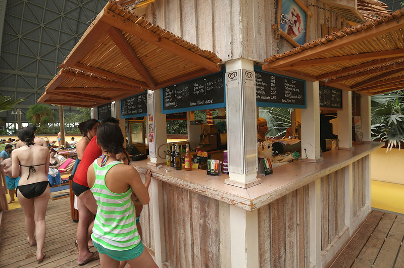". Visitors wait in line for refreshments at a bodega at the ""South Sea\"" beach at the Tropical Islands indoor resort on February 15, 2013 in Krausnick, Germany. Located on the site of a former Soviet military air base, the resort occupies a hangar built originally to house airships designed to haul long-distance cargo. Tropical Islands opened to the public in 2004 and offers visitors a tropical getaway complete with exotic flora and fauna, a beach, lagoon, restaurants, water slide, evening shows, sauna, adventure park and overnights stays ranging from rudimentary to luxury. The hangar, which is 360 metres long, 210 metres wide and 107 metres high, is tall enough to enclose the Statue of Liberty.  (Photo by Sean Gallup/Getty Images)"