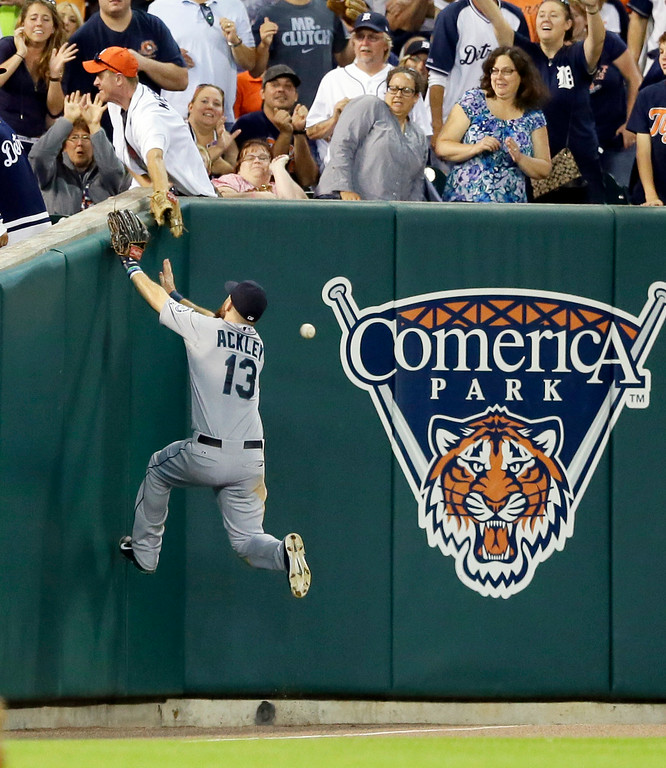 . Seattle Mariners left fielder Dustin Ackley goes after a foul ball hit by Detroit Tigers\' Ian Kinsler during the fifth inning of a baseball game, Friday, Aug. 15, 2014, in Detroit. (AP Photo/Carlos Osorio)