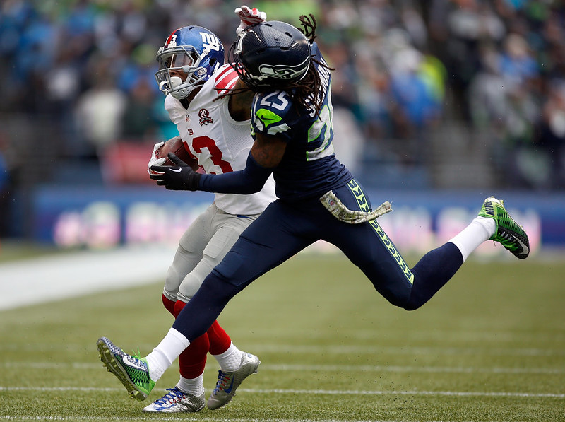. Wide receiver Odell Beckham Jr. #13 of the New York Giants gives Cornerback Richard Sherman #25 of the Seattle Seahawks a stiff arm during the second quarter of the game at CenturyLink Field on November 9, 2014 in Seattle, Washington.  (Photo by Otto Greule Jr/Getty Images)