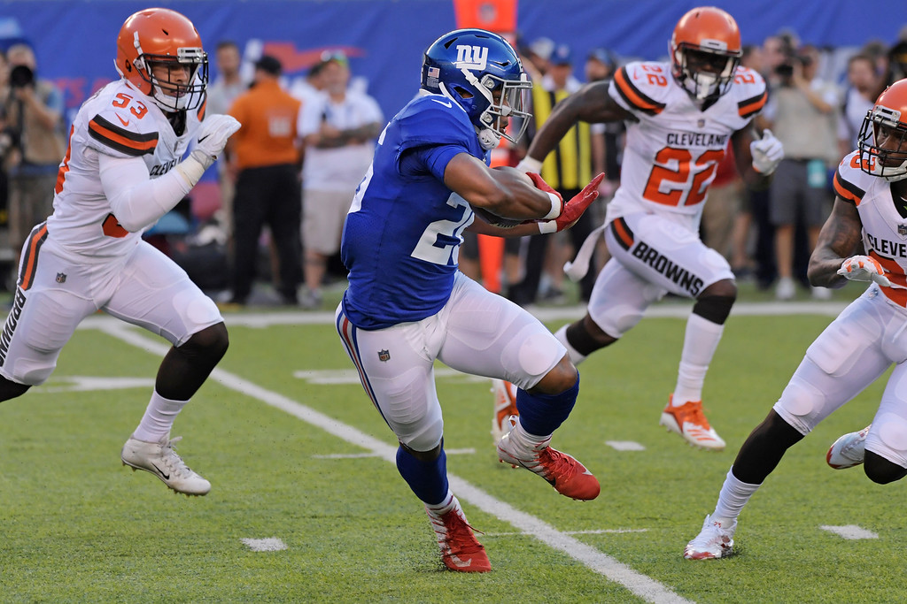 . New York Giants\' Saquon Barkley (26) rushes away from Cleveland Browns\' Jabrill Peppers (22) during the first half of a preseason NFL football game Thursday, Aug. 9, 2018, in East Rutherford, N.J. (AP Photo/Bill Kostroun)
