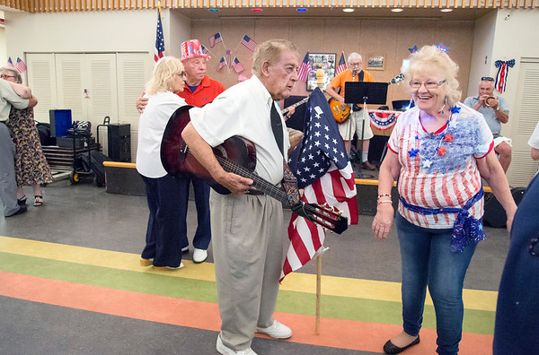 07/03/19 Wesley Bunnell | Staff The New Britain Senior Center was the scene for a 4th of July Red White & Boom Party presented by Autumn Lake on Wednesday July 3, 2019. The event featured food, raffle items and a live band. WWII Veteran Peter Spano takes to the dance floor carrying an American flag and a guitar as he dances with Donna Cutler.