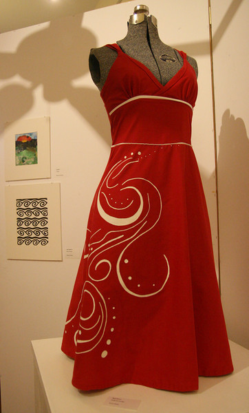 """""""Red Dress"""", an original design by Erica Rupp, is framed with the works of Monica Overmier and Rebecca Ennis in the background."""