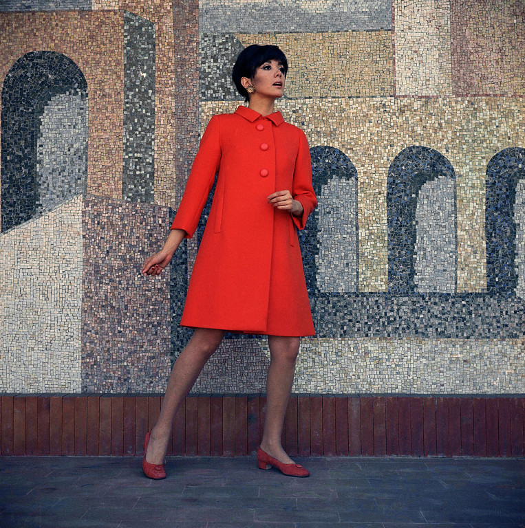 . An orange-red woolen coat, by Renato Balestra fashion house of Rome, modeled by Gilda Giuffrida. The coat can be worn over a dress of the same fabric and color, trimmed with buttons of the same fabric at the sleeves and at the hem of the dress fashion Italian coat in 1967. (AP Photo/Mario Torrisi)