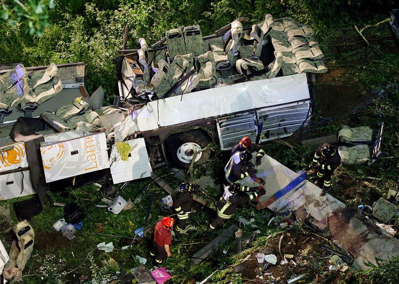. Firefighters work on the wreckage of a bus that plunged off the A16 highway near Avellino, southern Italy, early Monday, July 29, 2013. A tour bus filled with Italians plunged off a highway and fell into a ravine in southern Italy on Sunday night killing at least 37 people, police and rescuers said. Reports said as many as 49 people had been aboard the bus when it ripped through a guardrail after slamming into cars slowed down by traffic, then plunged some 30 meters (100 feet) off the highway and into a ravine near a wooded area. (AP Photo/Gregorio Borgia)