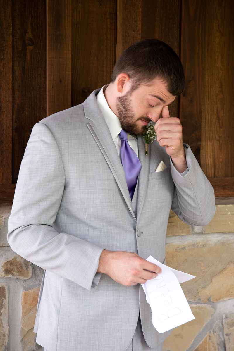 a groom wearing a grey suit and purple tie tearing up as he reads a letter from is soon-to-be wife