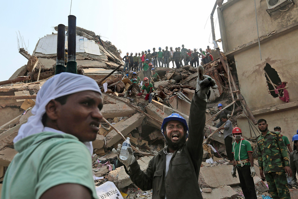 . A Bangladeshi rescuer shouts for assistance as another waits with a stretcher for injured or dead at the site of a building that collapsed Wednesday in Savar, near Dhaka, Bangladesh, Thursday, April 25, 2013.  (AP Photo/Kevin Frayer)