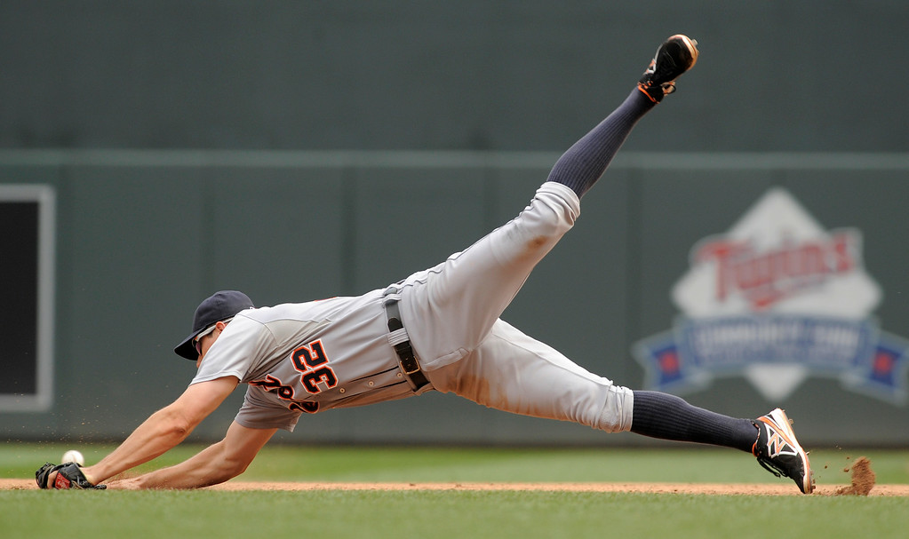 . Detroit Tigers first baseman Don Kelly misses a ground ball single off the bat of the Minnesota Twins\' Kennys Vargas during the fifth inning of a baseball game in Minneapolis, Sunday, Aug. 24, 2014. Detroit won 13-4.(AP Photo/Tom Olmscheid)