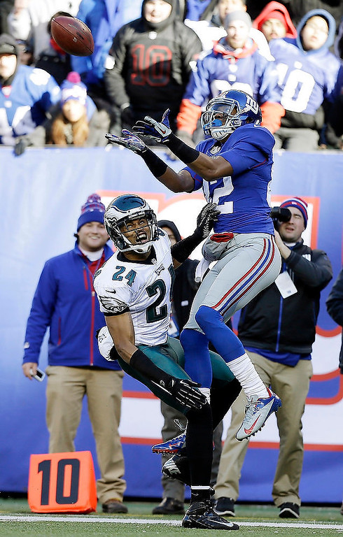 . New York Giants wide receiver Rueben Randle (82) catches a pass as Philadelphia Eagles cornerback Nnamdi Asomugha (24) defends during the first half of an NFL football game on Sunday, Dec. 30, 2012, in East Rutherford, N.J. (AP Photo/Kathy Willens)