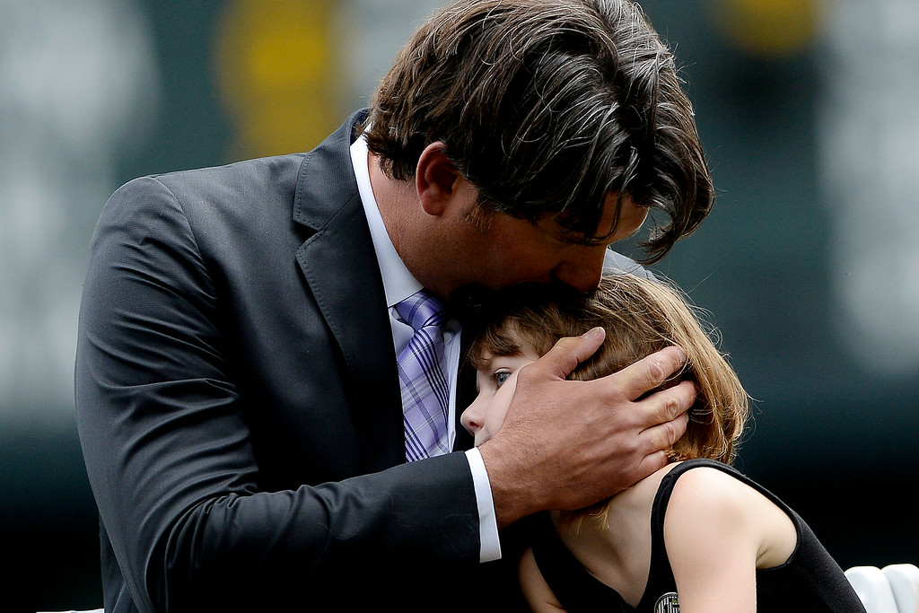 . Colorado Rockies great Todd Helton kisses his daughter, Gentry Grace, during a retirement ceremony for his number 17. Helton, who played 17 season with the Rockies and holds records for many of the organizations career statistics, was honored on Sunday, August 17, 2014. (Photo by AAron Ontiveroz/The Denver Post)
