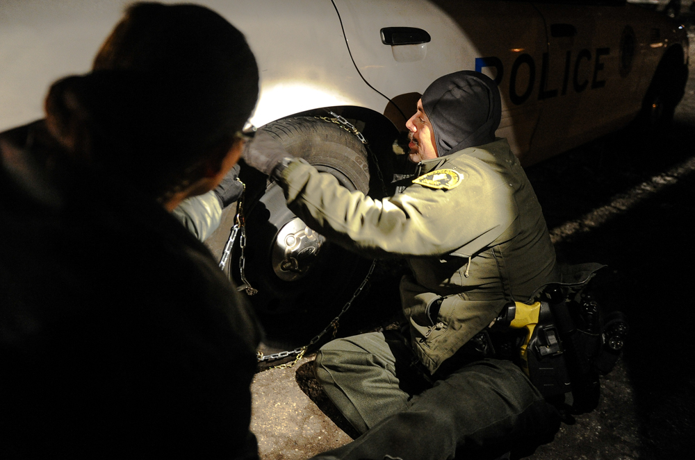 Description of . Sheriff's deputies from neighboring stations fit their patrol vehicle with snow chains as they prepare to leave the command post at Bear Mountain Resort at the closing of the third day in the search for fugitive ex-cop Christopher Dorner in Big Bear on Saturday, Feb. 9, 2013. Approximately 50 officers continued the search for Dorner Saturday. (Rachel Luna / Staff Photographer)