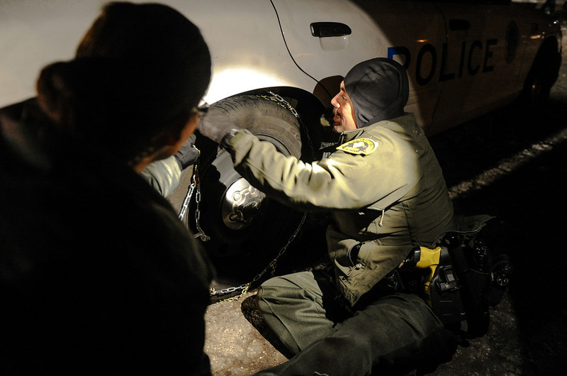 . Sheriff\'s deputies from neighboring stations fit their patrol vehicle with snow chains as they prepare to leave the command post at Bear Mountain Resort at the closing of the third day in the search for fugitive ex-cop Christopher Dorner in Big Bear on Saturday, Feb. 9, 2013. Approximately 50 officers continued the search for Dorner Saturday. (Rachel Luna / Staff Photographer)