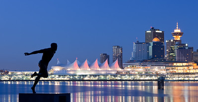 Night skyline of Vancouver BC from Stanley Park with statue of Harry Winston Jerome (BC's Athlete of the Century from 1871 to 1971) in the foreground